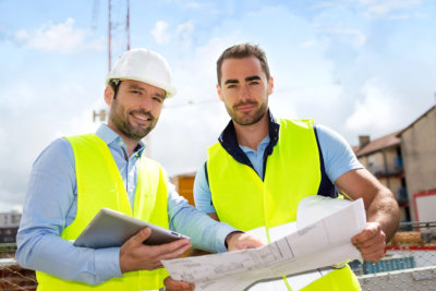 View of an Engineer and worker checking plan on construction site
