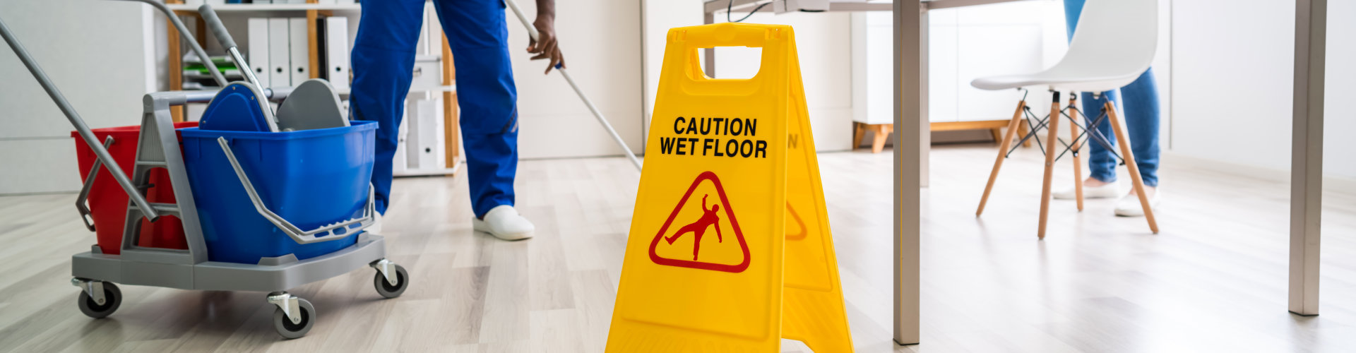 man using a wet floor sign while mopping